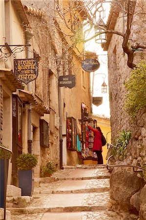 european - France, Alpes Maritimes Provence Cote d'Azur, Eze. Woman looking at items hanging outside a shop in the historical town Stock Photo - Rights-Managed, Code: 862-07495900