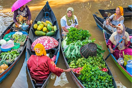Indonesia, South Kalimatan, Lok Baintan. Market vendors pause to chat at a picturesque floating market on the Barito River. Stock Photo - Rights-Managed, Code: 862-07909924