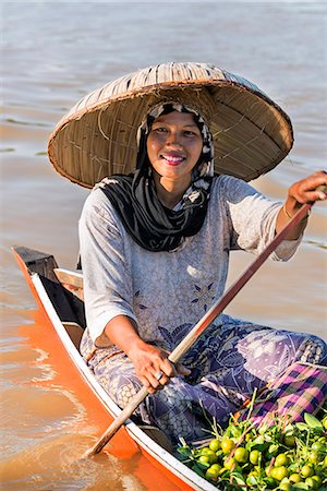 Indonesia, South Kalimatan, Lok Baintan. A woman in a wide-brimmed hat rows her small wooden boat at a floating market on the Barito River. Stock Photo - Rights-Managed, Code: 862-07909925