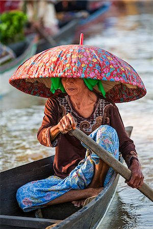 Indonesia, South Kalimatan, Lok Baintan. A market vendor in a wide-brimmed hat rows her small wooden boat at a floating market on the Barito River. Stock Photo - Rights-Managed, Code: 862-07909922