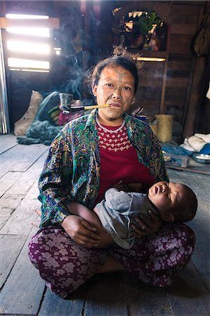 Myanmar, Chin State, Kempetlet. Chin woman with  traditional facial tattoo, holding her baby boy and smoking pipe. (MR) (PR) Stock Photo - Rights-Managed, Code: 862-07910308