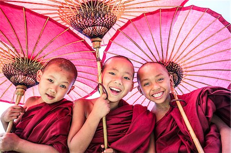 Myanmar, Mandalay division, Bagan. Portrait of three novice monks under red umbrellas (MR) Stock Photo - Rights-Managed, Code: 862-07910315