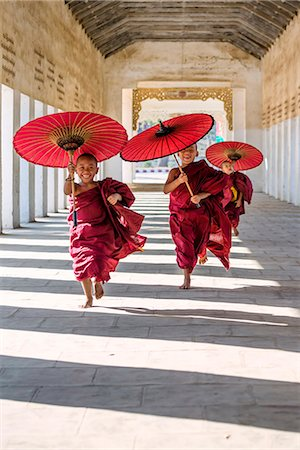people - Myanmar, Mandalay division, Bagan. Three novice monks running with red umbrellas in a walkway (MR) Stock Photo - Rights-Managed, Code: 862-07910318