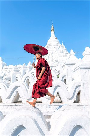 southeast asian ethnicity - Myanmar, Mandalay division, Mingun. Novice monk with red umbrella jumping on Hsinbyume Pagoda (MR) Stock Photo - Rights-Managed, Code: 862-07910325