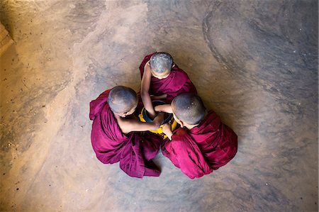 southeast asian ethnicity - Myanmar, Mandalay division, Bagan. Three novice monks with alms bowl, inside a pagoda (MR) Stock Photo - Rights-Managed, Code: 862-07910321