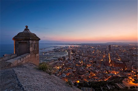 Sunset view over the cityscape of Alicante looking towards the lookout tower and Port of Alicante from Benacantil Mountain and Santa Barbara Castle in Ensanche Diputacion, Alicante, Valencian Community, Spain. Stock Photo - Rights-Managed, Code: 862-07910728