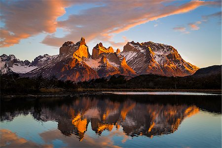 Chile, Torres del Paine, Magallanes Province. Sunrise over Torres del Paine reflected in the waters of Lake Pehoe in the foreground. One of the principal attractions of the National Park is the magnificent Paine massif. Stock Photo - Rights-Managed, Code: 862-08090054