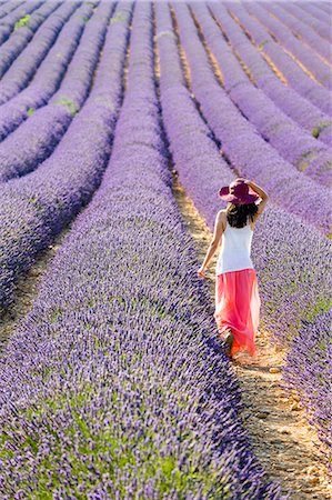smelly - Provence, France, Europe. Young girl walking through the purlple lavander fields full of flowers, with a hat on head and colourful long dress. Valensole Plateau Stock Photo - Rights-Managed, Code: 862-08273121
