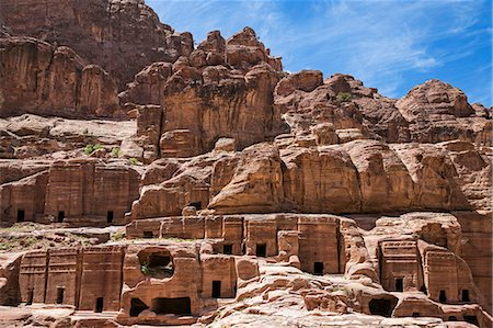 Jordan, Petra. Rows of Nabataean tombs with intricate designs were hewn into the pink sandstone hillside above the street of faþades in the ancient Nabataean city of Petra. Fotografie stock - Rights-Managed, Codice: 862-08273509