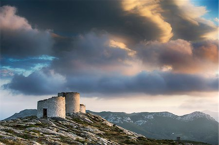 Greece, Amorgos, Chora. Derelict windmills under a dramatic sky at sunset. Stock Photo - Rights-Managed, Code: 862-08699272