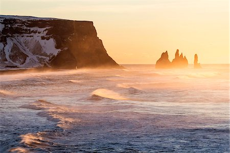 Vik, Southern Iceland, Europe.  The rock formations of Reynisdrangar and ocean waves at sunrise. Stock Photo - Rights-Managed, Code: 862-08699322