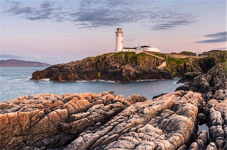 Fanad Head (Fánaid) lighthouse, County Donegal, Ulster region, Ireland, Europe. Panoramic view of the lighthouse and its cove at dusk. Stock Photo - Rights-Managed, Code: 862-08699391