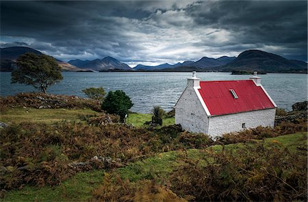 Scotland, Wester Ross. A brightly coloured cottage beside Loch Shieldaig on a gloomy day. Stock Photo - Rights-Managed, Code: 862-08699969