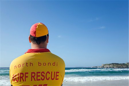 A lifesaver watches the surf on Bondi Beach in eastern Sydney. Lifesavers are a common sight on Australian beaches,assisting swimmers in distress. Stock Photo - Rights-Managed, Code: 862-03288859