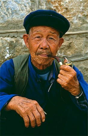 A Naxi man smokes his pipe Stock Photo - Rights-Managed, Code: 862-03289880