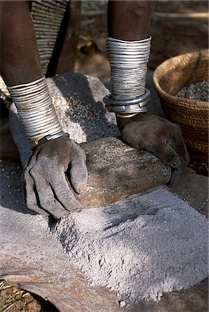 A Nyangatom woman grinds sorghum using two stones. Typical of her tribe,she wears a heavily beaded calfskin skirt,multiple layers of bead necklaces and metal bracelets and amulets. The Nyangatom or Bume are a Nilotic tribe of semi-nomadic pastoralists who live along the banks of the Omo River in south-western Ethiopia. Stock Photo - Rights-Managed, Code: 862-03354066