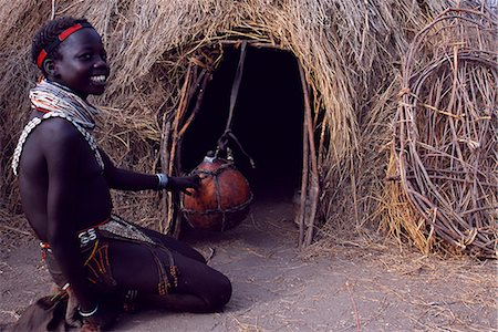 A Nyangatom girl churns butter in a gourd suspended in the entrance to her hut. Typical of her tribe,she is wearing multiple layers of beads in necklaces,and an elaborately beaded calfskin skirt. The Nyangatom or Bume are a Nilotic tribe of semi-nomadic pastoralists who live along the banks of the Omo River in south-western Ethiopia. Stock Photo - Rights-Managed, Code: 862-03354062