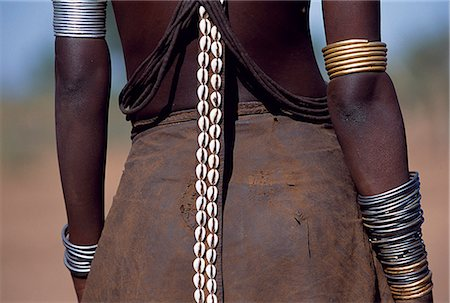 A young Dassanech girl wears a leather skirt,metal bracelets and amulets and layers of bead necklaces. A long leather strap decorated with cowrie shells hangs down her back. Much the largest of the tribes in the Omo Valley numbering around 50,000,the Dassanech (also known as the Galeb,Changila or Merille) are Nilotic pastoralists and agriculturalists. Stock Photo - Rights-Managed, Code: 862-03354075