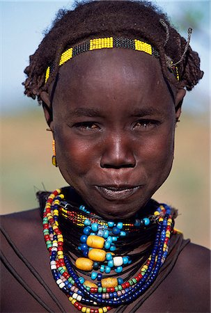 A young Dassanech girl wears a beautiful array of beaded necklaces. Much the largest of the tribes in the Omo Valley numbering around 50,000,the Dassanech (also known as the Galeb,Changila or Merille) are Nilotic pastoralists and agriculturalists. Stock Photo - Rights-Managed, Code: 862-03354078