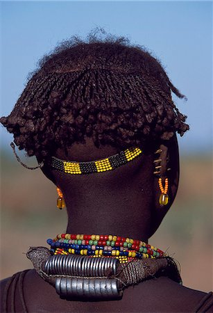 A young Dassanech girl wears a beautiful array of beaded necklaces,some secured at the back by metal rings,and a beaded headband. Her ears are pierced several times,the holes are kept open by small wooden plugs. Much the largest of the tribes in the Omo Valley numbering around 50,000,the Dassanech (also known as the Galeb,Changila or Merille) are Nilotic pastoralists and agriculturalists. Stock Photo - Rights-Managed, Code: 862-03354079
