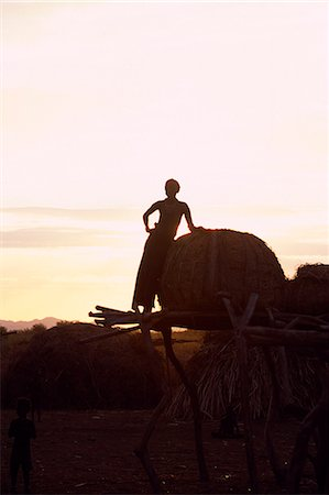 A Dassanech girl leaning against a bale of cattle fodder on a raised platform is silhouetted against the evening sky at a settlement alongside the Omo River. Much the largest of the tribes in the Omo Valley numbering around 50,000,the Dassanech (also known as the Galeb,Changila or Merille) are Nilotic pastoralists and agriculturalists. Stock Photo - Rights-Managed, Code: 862-03354087