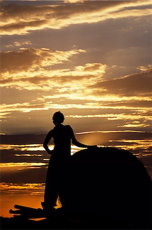 A Dassanech girl leaning against a bale of cattle fodder on a raised platform is silhouetted against the evening sky at a settlement alongside the Omo River. Much the largest of the tribes in the Omo Valley numbering around 50,000,the Dassanech (also known as the Galeb,Changila or Merille) are Nilotic pastoralists and agriculturalists. Stock Photo - Rights-Managed, Code: 862-03354088