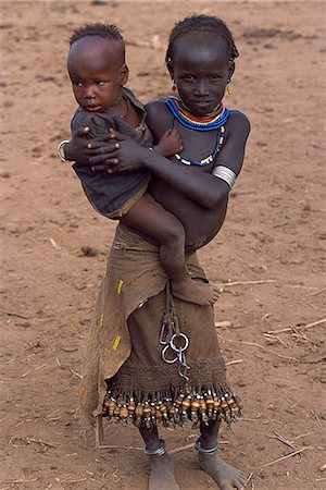 A young Dassanech girl holds her little brother. She wears a leather skirt with an elaborate fringe of wooden and metal tassles. Much the largest of the tribes in the Omo Valley numbering around 50,000,the Dassanech (also known as the Galeb,Changila or Merille) are Nilotic pastoralists and agriculturalists. Stock Photo - Rights-Managed, Code: 862-03354081