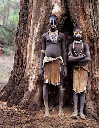 Two young Karo girls stand in front of the massive trunk of a fig tree. A small Omotic tribe related to the Hamar,who live along the banks of the Omo River in southwestern Ethiopia,the Karo are renowned for their elaborate body painting using white chalk,crushed rock and other natural pigments. Stock Photo - Rights-Managed, Code: 862-03354095
