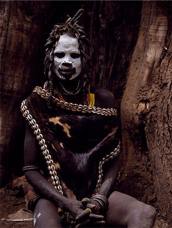 A Karo woman wears an elaborate headdress made from the wing-cases of beetles and a cape of calf skin fringed with cowrie shells. A small Omotic tribe related to the Hamar,who live along the banks of the Omo River in southwestern Ethiopia,the Karo are renowned for their elaborate body painting using white chalk,crushed rock and other natural pigments. Stock Photo - Rights-Managed, Code: 862-03354096