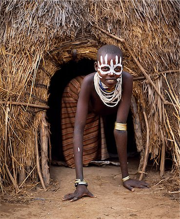A young Karo girl in the doorway of her hut in the village of Duss. A small Omotic tribe related to the Hamar,who live along the banks of the Omo River in southwestern Ethiopia,the Karo are renowned for their elaborate body painting using white chalk,crushed rock and other natural pigments. Stock Photo - Rights-Managed, Code: 862-03354098