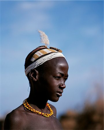 A young Dassanech boy with an elaborate clay hairdo and headband of beads at his village in the Omo Delta. Much the largest of the tribes in the Omo Valley numbering around 50,000,the Dassanech (also known as the Galeb,Changila or Merille) and Nilotic pastoralists and agriculturalists. Stock Photo - Rights-Managed, Code: 862-03354100