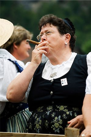 A woman smoking a cigar at the Unspunnen Festival Bicentenary,Interlaken,Jungfrau Region,Switzerland Stock Photo - Rights-Managed, Code: 862-03354678