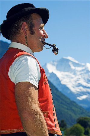 A Swiss man smoking a pipe in traditional alpine costume at the Unspunnen Bicentenary Festival,Interlaken,Jungfrau Region,Switzerland Stock Photo - Rights-Managed, Code: 862-03354682