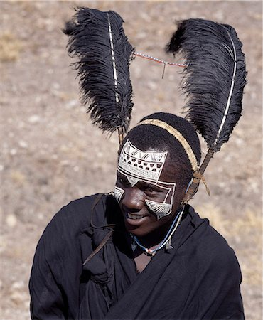 Black clothing,Black ostrich feathers and the intricate white patterns on the face of this Maasai youth of the Kisongo section signify his recent circumcision. Stock Photo - Rights-Managed, Code: 862-03355129