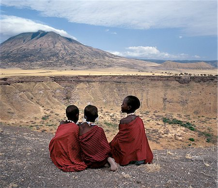 Three Maasai girls sit on the edge of Shimu la Mungu (a volcanic blow hole known as 'God's hole') with the extinct volcano,Kerimasi,in the distance. Stock Photo - Rights-Managed, Code: 862-03355144