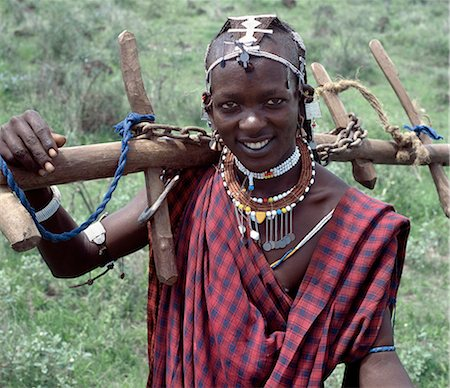 A Wa-Arusha warrior carries home a yoke. His brown necklace is made from aromatic wood. The Wa-Arusha are closely related to the Maasai and speak the same maa language. Unlike the Maasai,however,they till the land. In the past,this has brought them into conflict with their pastoral neighbors who disdained cultivation. Stock Photo - Rights-Managed, Code: 862-03355140