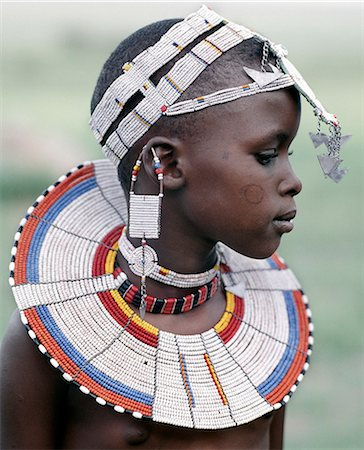 A Maasai girl in traditional attire. The predominant white colour of her beadwork and the circular scar on her cheek denote that she is from the Kisongo section of the Maasai,the largest clan group,which lives either side of the border in Kenya and Tanzania. Stock Photo - Rights-Managed, Code: 862-03355141