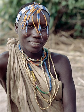 A Hadza girl wearing a beaded headband and necklaces.The Hadzabe are a thousand-strong community of hunter-gatherers who have lived in the Lake Eyasi basin for centuries. They are one of only four or five societies in the world that still earn a living primarily from wild resources. Stock Photo - Rights-Managed, Code: 862-03355175
