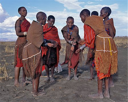 Old Datoga women wearing beautifully tanned and decorated leather dresses sing a short distance from their homes. They keep rhythm by rubbing their numerous iron bracelets together.The Datoga (known to their Maasai neighbours as the Mang'ati and to the Iraqw as Babaraig) live in northern Tanzania and are primarily pastoralists. Stock Photo - Rights-Managed, Code: 862-03355205