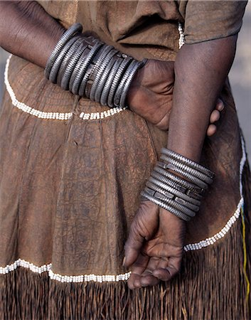 The numerous decorated iron bracelets worn by a Datoga woman. During song and dance,she will rub them together to keep rhythm. Her traditional attire includes a beautifully tanned leather dress embellished with beads. The Datoga (known to their Maasai neighbours as the Mang'ati and to the Iraqw as Babaraig) live in northern Tanzania and are primarily pastoralists. Stock Photo - Rights-Managed, Code: 862-03355207