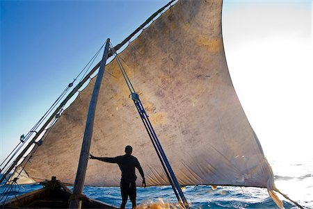 East Africa,Tanzania. Sailing an Arab dhow in Zanzibar. A dhow is a traditional Arab sailing vessel with one or more lateen sails. It is primarily used along the coasts of the Arabian Peninsula,India,and East Africa. Stock Photo - Rights-Managed, Code: 862-03355257