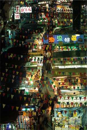 Shoppers converge on the shopping bargains of the Temple Street night markets in Kowloon,Hong Kong. The popular market is a hub for cheap clothes,food,watches and fake designer wares. Stock Photo - Rights-Managed, Code: 862-03350947