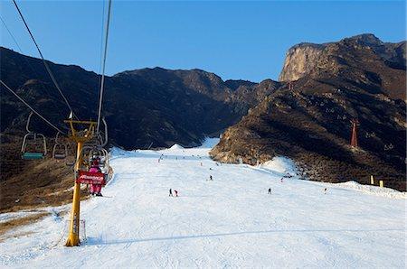 China,Beijing,Shijinglong ski resort. A ski lift taking skiers up to the slopes. Stock Photo - Rights-Managed, Code: 862-03351466