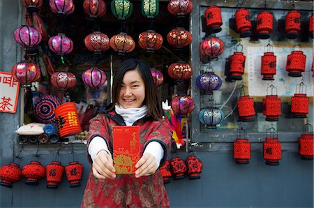 China,Beijing. A Chinese girl wearing traditional Chinese style clothes holding a Hongbao envelope which is received with money by students and children during Chinese New Year Spring Festival . Stock Photo - Rights-Managed, Code: 862-03351513