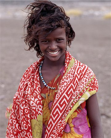 A pretty tousle-haired girl of the nomadic Afar tribe wears bright colours in stark contrast to the drab,windswept surroundings of Lake Abbe. Stock Photo - Rights-Managed, Code: 862-03352642