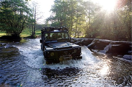 England,Somerset,Exmoor. The ford at Tarr Steps is waded by a four wheel drive - a Landrover Defender 110 with the prehistoric clapper bridge on the right hand side. Stock Photo - Rights-Managed, Code: 862-03353605