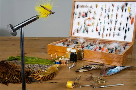 A traditionally tied salmon fly pattern called a Yellow eagle in the vice on a fly-tiers bench Stock Photo - Rights-Managed, Code: 862-03353761