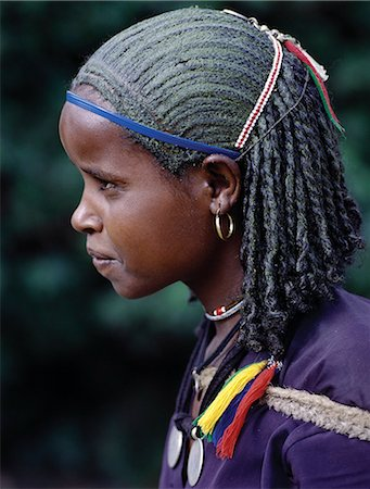 A young Ethiopian girl with unusual braided hair; the crown of her head has been smeared with a greenish substance. Her two pendants are made from Maria Theresa thalers old silver coins minted in Austria,which were widely used as currency in northern Ethiopia and Arabia until the end of World War II. Stock Photo - Rights-Managed, Code: 862-03353964