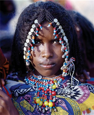 An Afar girl has her attractive hairstyle embellished with buttons and beads,which is typical of the young girls of her tribe. Proud and fiercely independent,the nomadic Afar people live in the low-lying deserts of Eastern Ethiopia. Stock Photo - Rights-Managed, Code: 862-03353972
