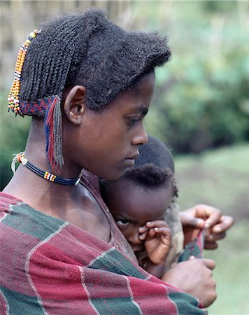A young mother and child of the Arsi-Oromo people west of Aje. Both have unusual hairstyles. The braids falling from the crown of the mother's head have been attractively woven with wool to make a colourful fringe. Stock Photo - Rights-Managed, Code: 862-03353994